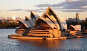 Syney Opera House taken from a ship at sunset - the House glows yellow and orange